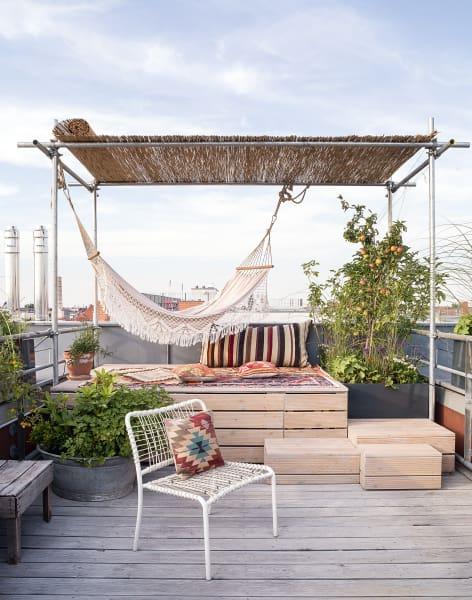 Auf ihrer Dachterrasse baute sie eine einladende Lounge, die noch genug Platz lässt für eine ihrer Leidenschaften: Gartenarbeit in luftiger Höhe. Natürlich designte sie auch die Holzpodeste selbst.