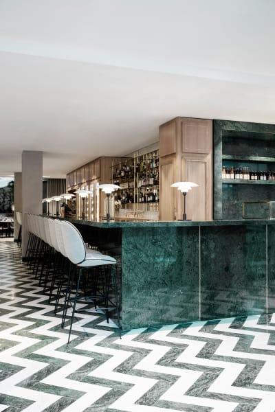 """Eleganter schwarz-weißer Marmorboden, verlegt im Fischgrätenmuster. An der Bar: Gubi´s Beetle Bar Chair""""."""