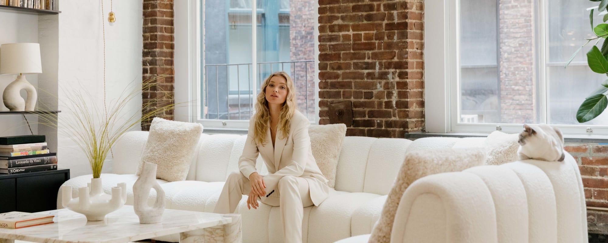 Elsa Hosk auf einem Bouclé-Sofa in ihrer Wohnung.
