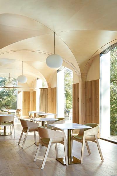 Helle Holzgewölbe aus vorgefertigten Modulen verweisen auf das Erbe des        Anwesens, einen alten Landsitz von 1880 in Kent. Der        helle, schlichte Innenraum erinnert an die Orangerie, die dort einst        stand, und fasst bis zu 50 Gäste.