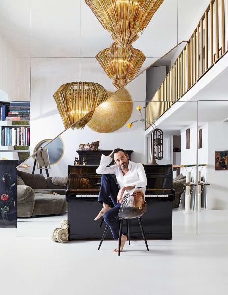 """Mit """"Gilda B."""" am Klavier: Jacopo Foggini in seinemMailänder Loft, wo er unter dem goldenen Feuerwerk seiner Lüster """"Brilli"""" für Lumisol und der Applike """"Tondo"""" (im Spiegel miteiner Tigerfigur aus Tibet) eine Kunstpause einlegt."""
