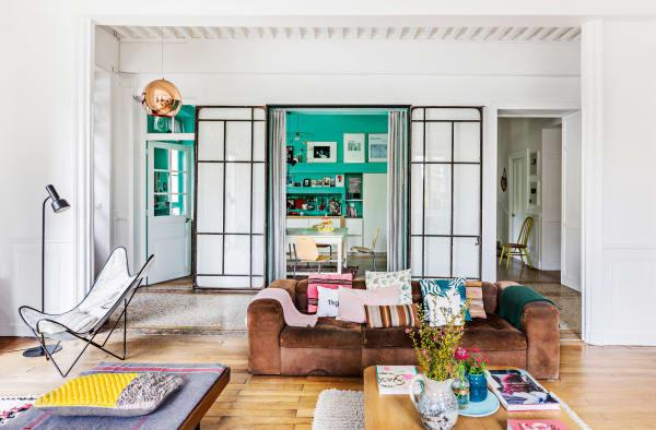 Ein Wildledersofa von Zanotta aus den Siebzigern prägt den Wohnraum im        Erdgeschoss Auf ihm liegen Kissen von Honoré Décoration und Maison Bensimon. Die Plaids strickte Marine Palayer selbst, die Decke auf dem        Daybed ist von Merci.