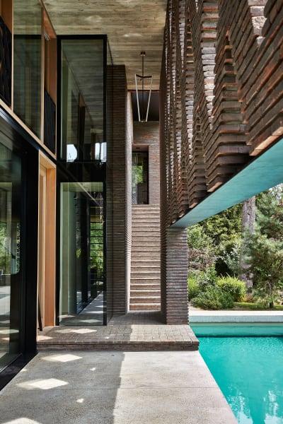 """Der Steinvorhang schützt vor aufdringlichen Sonnenstrahlen und lässt trotzdem genügend Licht ins Haus. """"Und wenn es regnet, können wir immer noch draußen sein"""", sagt Alex Gabriels, deren über die Treppe erreichbares Studio über dem Wohnzimmer liegt und Baumblick bietet."""