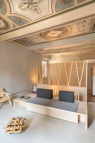 """Durch Entfernen einer nicht tragenden Wand entstand der große Wohn- und Schlafraum. Die extratiefe Bank ist auch als  Coffeetable nutzbar. EliaPavesi entwarf das mobile Leuchtobjekt vorn. Unter dem Namen """"Broletto Uno"""" ist das Apartment über Airbnb zu buchen, 150Euro pro Nacht."""
