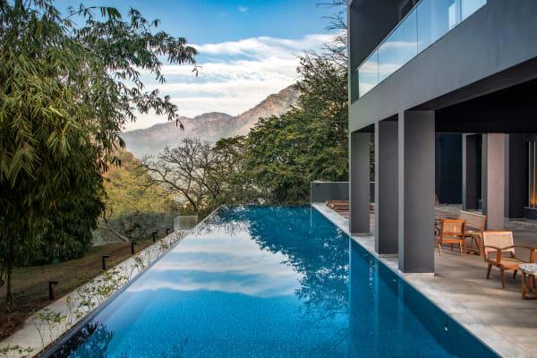 """In öffentlichen        Bereichen, etwa vom beheizten Infinity Pool aus, soll nichts von Wald        und Bergen ablenken. """"Die Natur ist mächtiger als die Architektur"""",        betont Ankur Bhatia."""