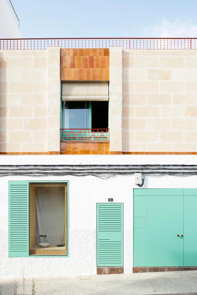 Die glasierten Terrakotta-Fliesen Miquel Solers säumen die neu aufgesetzte Wohnetage und rahmen das leuchtend türkise Fenster inmitten der sandfarbenen Steinfassade.