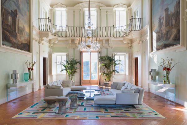 """Die Eigentümer empfanden den Salon als zu kühl, heute gibt ihm ein Teppich aus der Galleria Boralevi Struktur. Coffeetable und Konsolen von Glas Italia, umgeben von Flexform-Sofas. Die Platner-Hocker sind von Knoll, die Leuchten """"Steel Love"""" entwarf Willy Rizzo."""