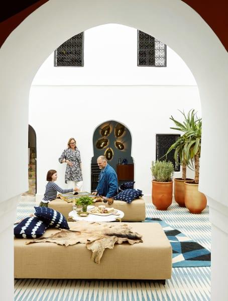 """Der Innenhof von Dar Noury trägt """"Backgammon""""-Fliesen in """"Slate"""" und """"Milk"""". Zur ersten Home-Collection von Caitlin und Samuel Dowe-Sandes (hier mit Tochter Georgina) gehören die """"Golden Egg""""- Leuchten im Hintergrund."""