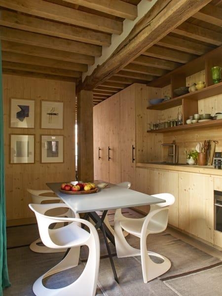 """Plastik? """"Nein, Glasfaser!"""" Die Küchenstühle sind von Steen Østergaard, aus einem Stück gebogen -und """"so bequem, dass wir stundenlang an meinem Esstisch aus lackiertem Stahl und Keramik sitzen"""", erklärt Delcourt. Grafiken von Károly Keserü und Thomas Müller."""