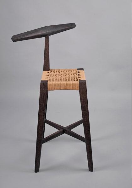"""Der Stuhl als Mittler zwischen Architektur und Kleidung – dieser        Gedanke inspirierte Isabelle Moore, Textilien in ihre charismatischen        Entwürfe zu integrieren. """"Woven Oak Stool"""" aus Eiche und Geflecht, 2025        Euro."""