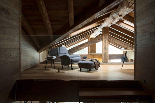 """Das Arbeitszimmer im Mezzanin (der Dachbalken stammt von einer alten Kirche im Piemont) ist der Lieblingsraum der Roveres. In Vico Magistrettis Sessel """"Louisiana"""", DePadova, sagt die Hausherrin, sei es """"unmöglich, nicht einzuschlafen"""" – erst recht nicht unter Ivano Redaellis Decke."""