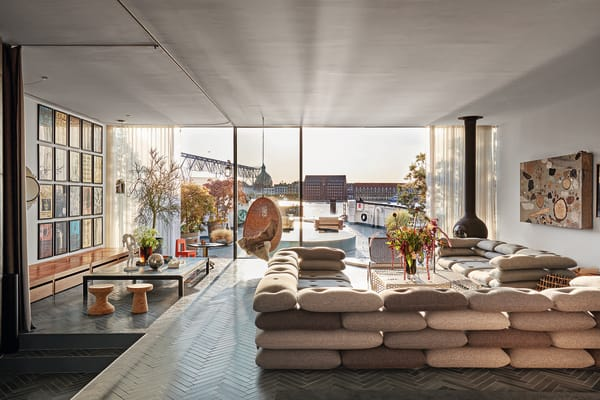 Hafenansicht: Große Glasfenster von Sky-Frame geben den Blick auf das        Wasser frei. Das Sofa von KiBiSi (eine Marke, die Ingels mitgründete)        erinnert an geschichtete Sandsäcke. Neben einem Kunstwerk von Katja        Schenker schwebt ein Kamin von Focus. Auf dem Boden:        marokkanische Betonfliesen.