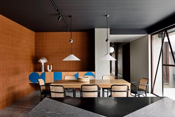 """Im Esszimmer dominiert der Dreiklang von Rostrot, Grau und Schwarz das minimalistische Bild von Architektur. Um den Tisch von Mark Tuckey stehen Thonets """"A811""""-Stühle. Deckenleuchte von Artemide, das Sideboard ist von Kennedy Nolan, die """"Shogun""""-Leuchte darauf von Mario Botta."""