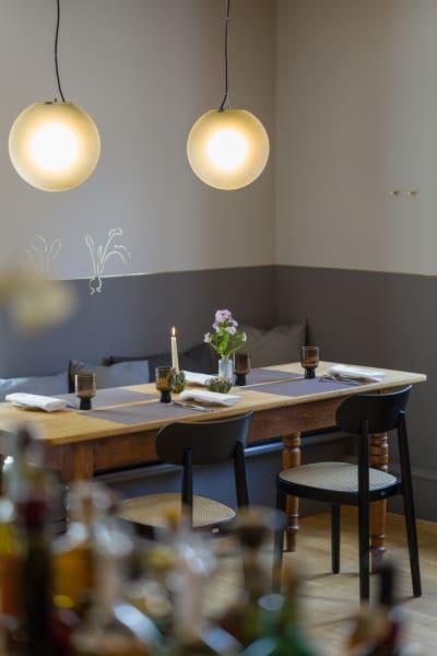 Die Messinglinie, die den gesamten Raum umläuft, formt Silhouetten von Gemüse und Tieren, die sich auf die regionalen Zutaten der Küche beziehen.