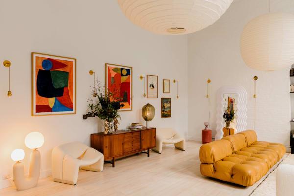 Gipfel der Designkoryphäen: Im Wohnzimmer von Elsa Hosk treffen Laternen von Isamu Noguchi auf ein Sofa von Mario Bellini, Sessel von Pierre Paulin und Gemälde von Caroline Denervaud. Die Bodenleuchte von Eny Lee Parker kaufte Hosk bei einem Besuch im Atelier der Designerin.