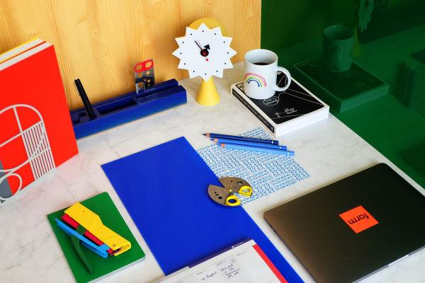"""Grünes Notizbuch """"Edge"""" vonHay, 8 Euro. Scheren """"Amazing Scissor"""" und Buchstütze """"Grid Bookend"""" vonPresent & Correct, 20 bzw. 35 Euro. Uhr """"Ceramic Clock, Model #2"""" von Vitra neben Organizer vonNormann Copenhagen. Rotes und gelbes Notizbuch in DINA4 von Fantastic Paper, 13 Euro. Schwarzer Füllfederhalter """"Montblanc M"""" vonMontblanc, 550 Euro. Tischkalender """"Le Module"""" vonPapier Tigre, 10 Euro. Tacker """"Tutti Frutti"""" überChoosing Keeping, 20 Euro.Apple MacBook Promit Touch Bar ab 1999 Euro."""