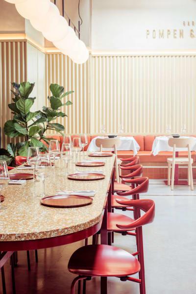Die Tischplatte aus Terrazzo, die magentafarbenen Stühle und die verspielten Kugelleuchten erinnern so gar nicht an die ehemalige Werkstatt.