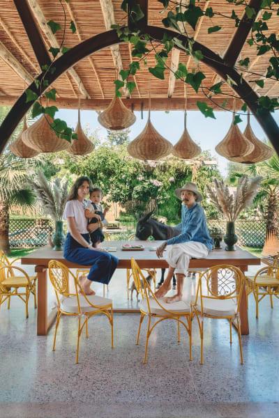 """Happy together: Cyrielle Rigot und Julien Phomveha mit Sohn Nino Bandith und Esel Kawa auf der Terrasse ihrer Farm. Die Strohleuchten und die honiggelben Stühle sind von Kunsthandwerkern aus der Umgebung. """"Uns ist es wichtig, Materialien lokal zu beziehen."""""""