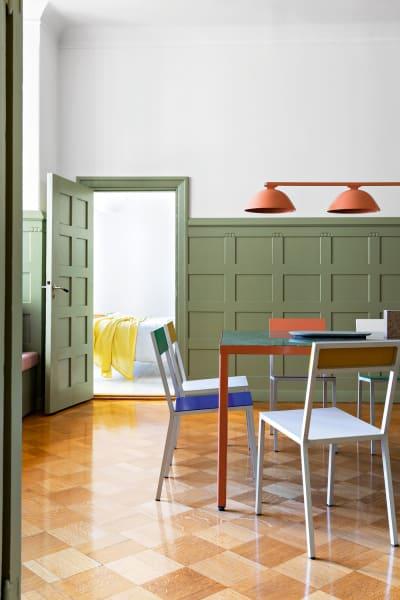 """Streichen statt rausreißen: Die Wandpaneele waren so hochwertig, dass sie noch 100 Jahre später makellos sind. Linda Bergroth ließ sie im frischen Farrow&Ball-Grün (Ton """"Lichen"""") streichen. Der Tisch ist von ihr, die Stüh‑ le entwarfen Muller Van Severen und die Deckenleuchte Inga Sempé."""