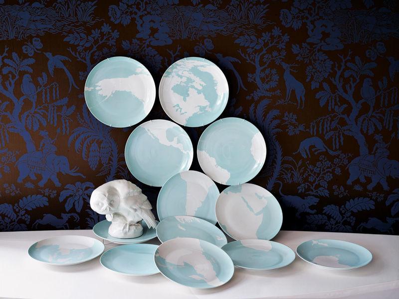 """Im Blauen Salon lauert eine Eule aus Biskuitporzellan auf einem Teller von Barnaby Barfords """"Global Service"""", das wie ein Puzzle die Weltkarte in Einzelteilen abbildet."""