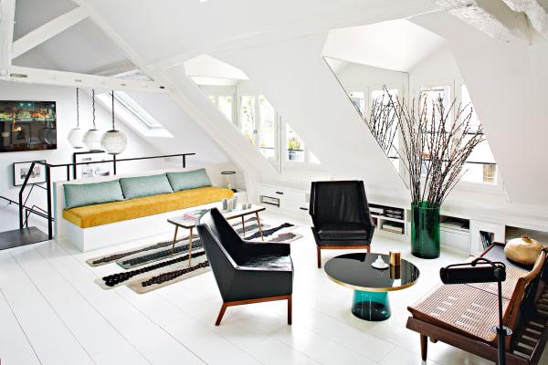 """""""Hell, warm und lebendig"""" wünschte sich Interiordesignerin Sarah Lavoine ihr Dach-Apartment in Paris. Sie strich deshalb Schrägen (mit Stauraum), Balken und Böden weiß, Spiegel in den Gaubenwangen lassen den Raum noch heller und weiter scheinen. Farbige Möbel und Accessoires und großformatige Kunst an den (geraden!) Wänden verhindern, dass es zu clean wirkt."""