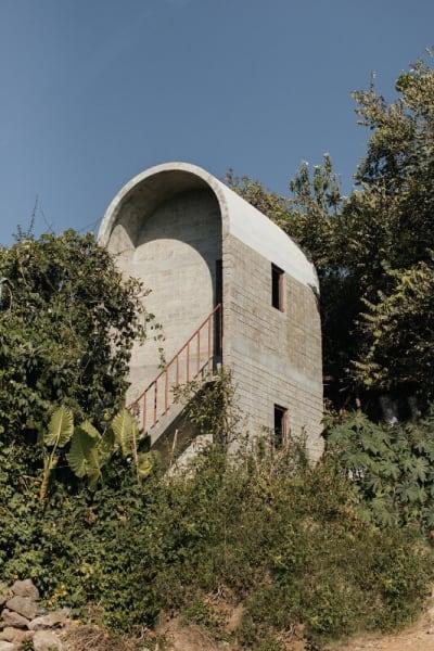 So sanft geht das Gebäude in seine Umgebung über: Mittels des Betongewölbes wird auf die umliegenden Berge verwiesen und auf das regnerische Klima der Region reagiert.