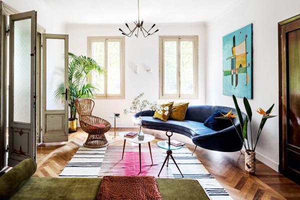 """Das Parkett und die Tür zum Wohnzimmer gehören zur Originalausstattung. Manuel Gazzola entwarf das geschwungene Sofa auf Messingbeinen, das Tischchen mit Marmorplatte ist von Giacomo Totti. Rattansessel """"Margherita"""" von Franco Albini."""