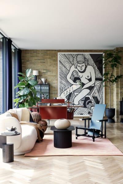 """Im Wohnzimmer entschied sich das Paar für Sofa """"Rico"""" und Couchtisch """"Podia"""" von Ferm Living, davor Gerrit Rietvelds """"364"""". Im hinteren Bereich des Raumes platzierten sie den Schreibtisch von Frank Lloyd Wright. Über allem ruht ein Kunstwerk von Christoph Rückhäberle."""