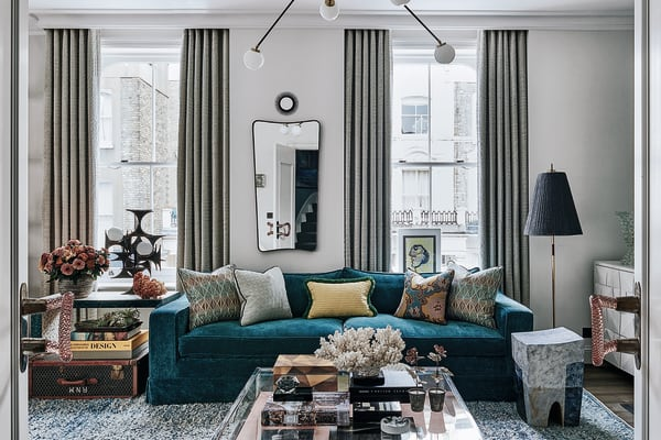 """Das blaue Sofa entwarf HZI, es wurde mit einem Rubelli-Stoff bezogen. Die weiße Kommode rechts stammt ebenfalls von HZI. Die Bezüge der Kissen sind von Opuzen, Dedar, Turnell&Gigon und Tibor Ltd. Die Stehleuchte ist 50er-Jahre-Vintage. Alt ist auch der Coffeetable aus Plexiglas: 70er-Jahre – Hubert Zandberg versah ihn mit einem Boden, den er mit """"Ultrasuede"""" von Toray bespannte."""