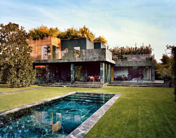 Aus einem Guss: Verde Alpi, ein grüner Marmor aus dem Valle d'Aosta, bedeckt Pool, Fassade und Terrassen der Villa. Bodentiefe Fenster und Geländer aus Glas betonen den pavillonartigen Charakter des Baus. Vonoben wirkt die dichte Dachbegrünung wie Schutzschirm und Tarnkappe zugleich.