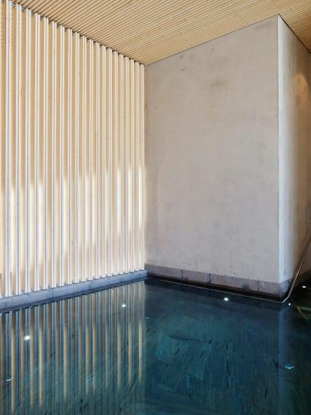 Für die einfachen minimalistischen Innenräume, die vor allem aus Sichtbetonwänden, Steinböden und Holzlamellen bestehen, wurde eine zurückhaltende Palette verwendet.