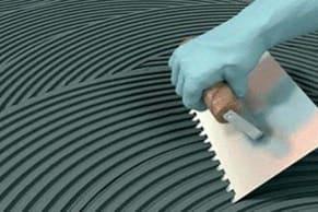 Como assentar porcelanato espalhando a argamassa colante na base