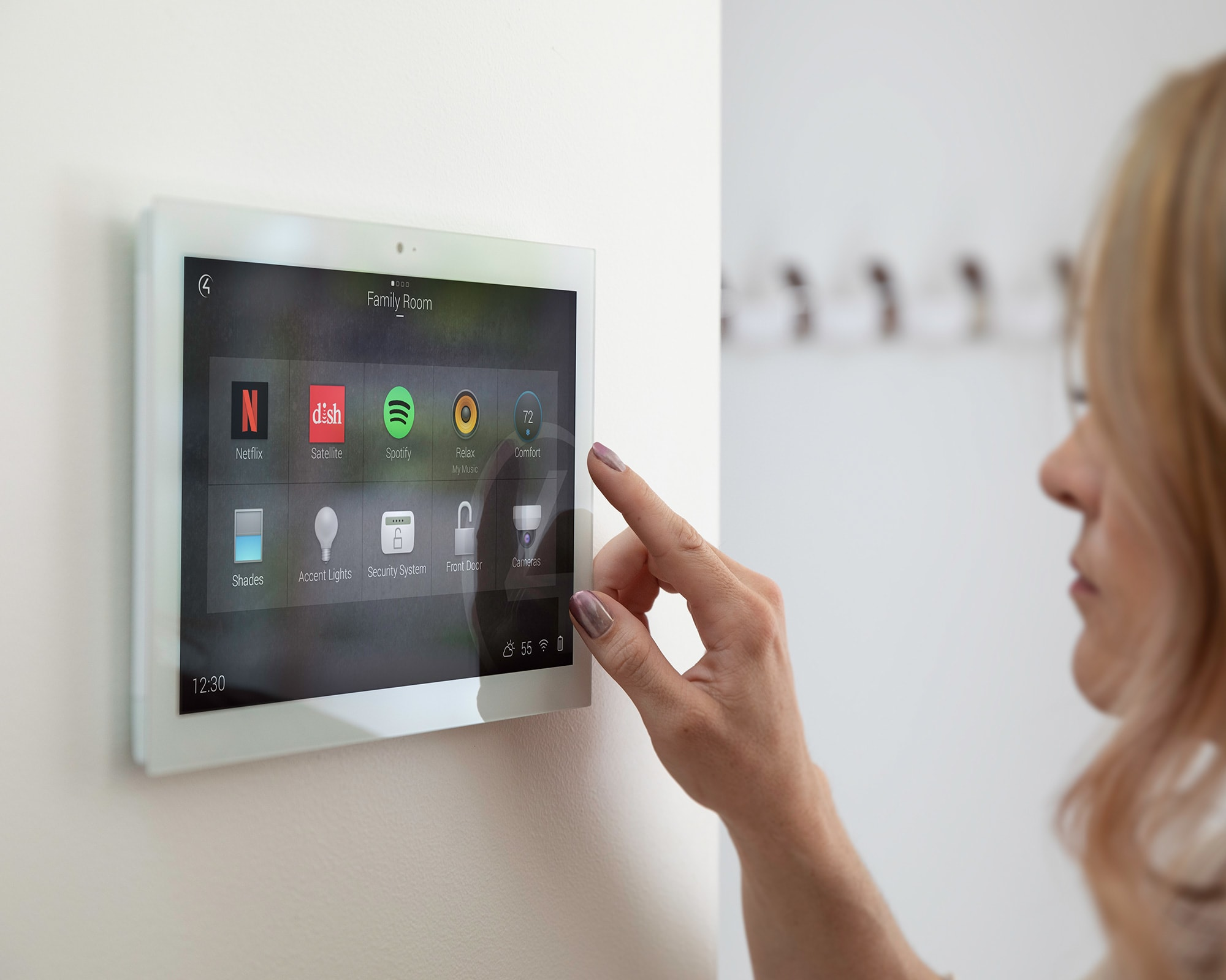 Woman interacting with Control4 smart home OS 3 on in-wall touch screen