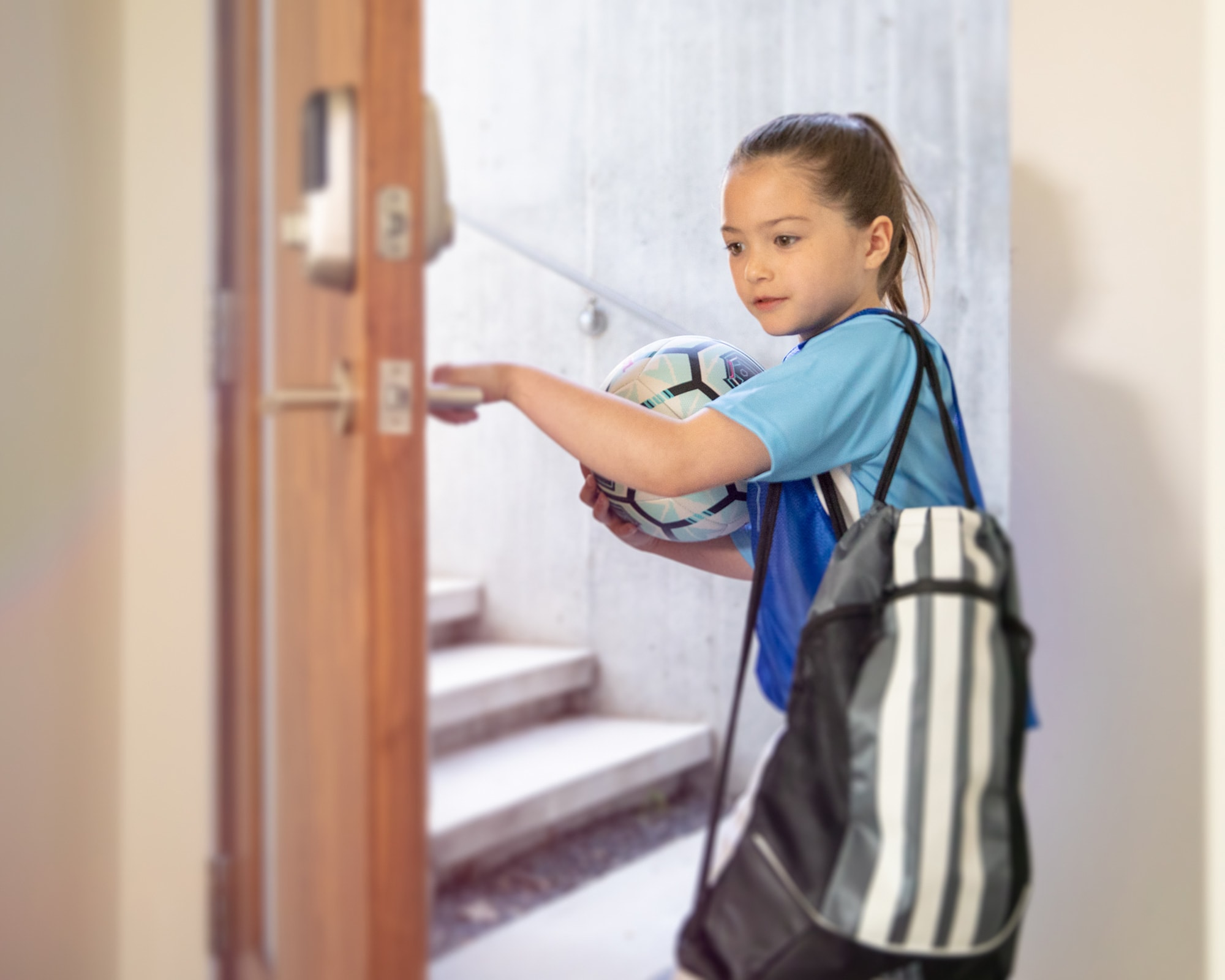 Child caring soccer ball entering home using connected smart door locks