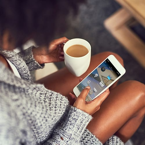 Woman drinking coffee while she uses the Control4 Mobile App to manage the devices in her home