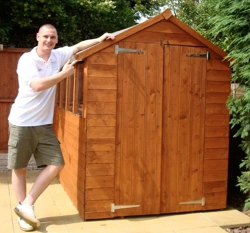 A photo of Ben next to his assembled shed.