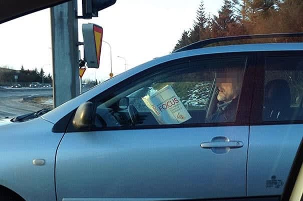 Man reading a book about focus while driving.