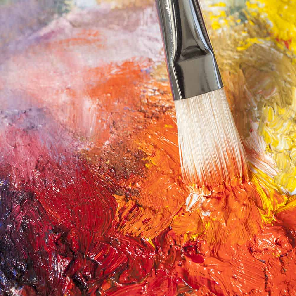 A brush being stroked through paint