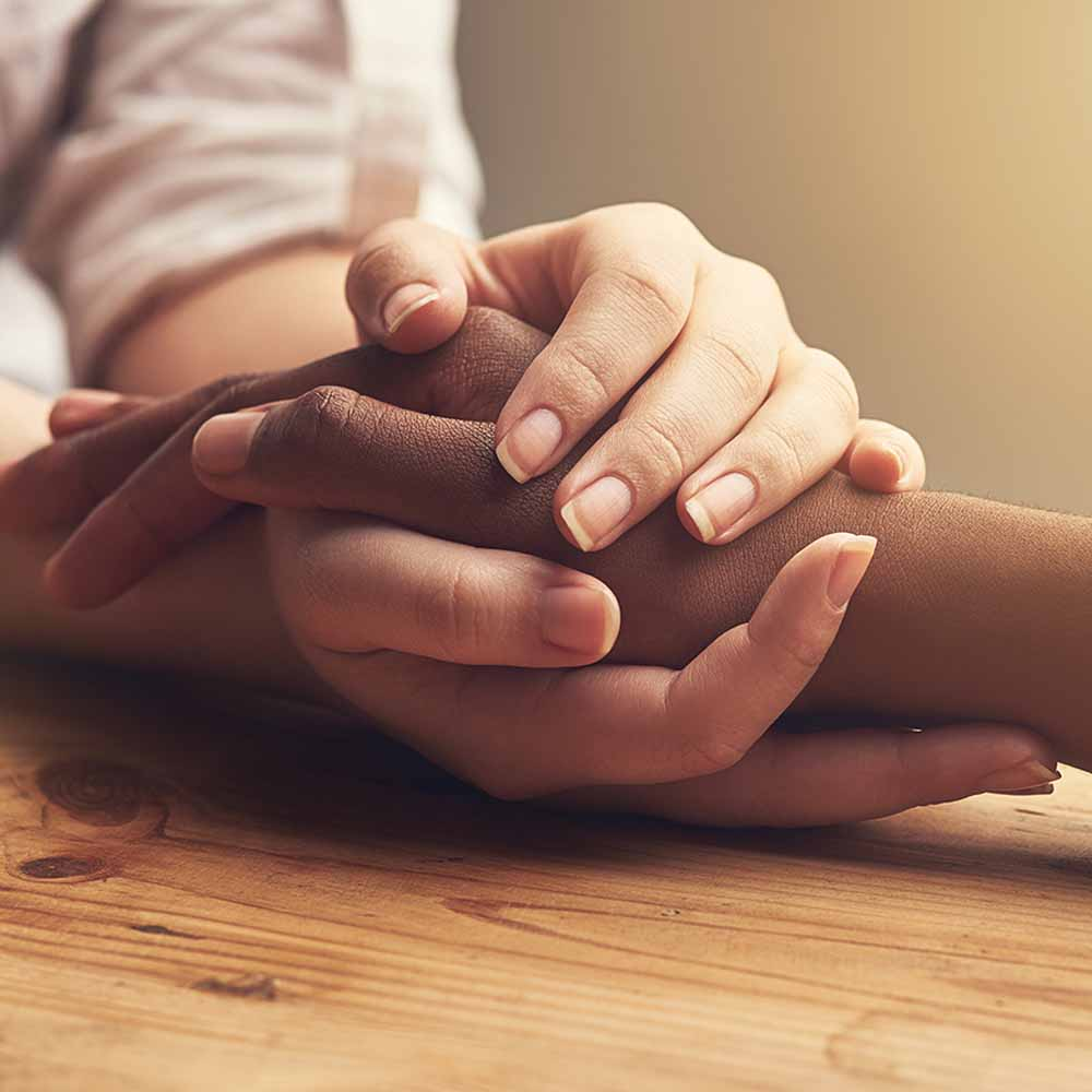 2 people holding hands resting on a wooden table