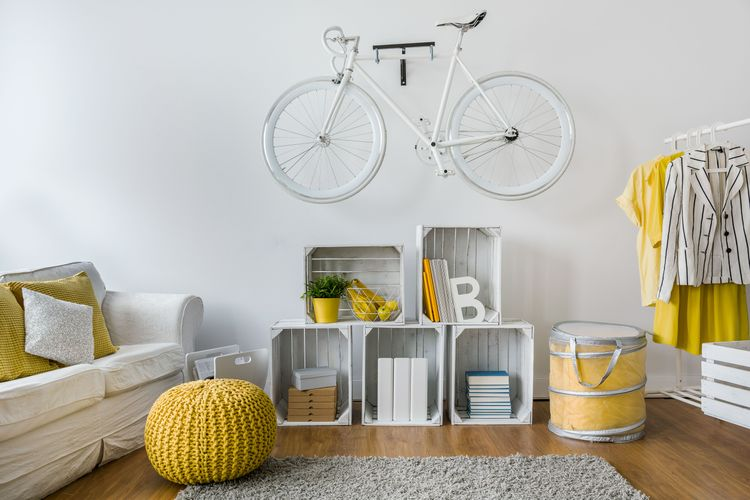 White wall with hanging bike, wooden floor boards