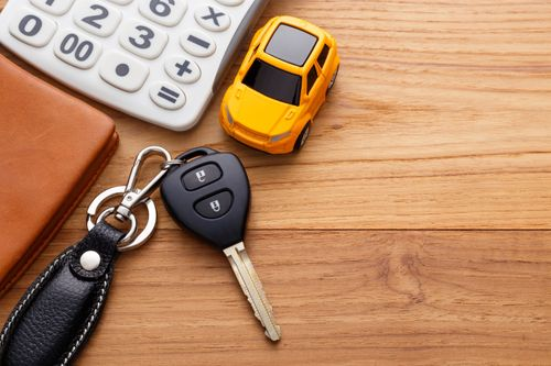 Keys and toy car with wallet and calculator sitting on a wooden desk