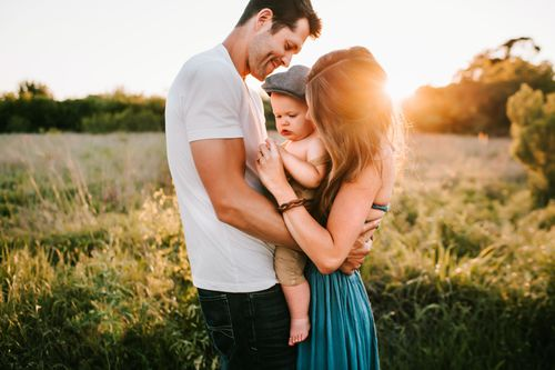 Man woman and baby standing in field of flowers with sunset