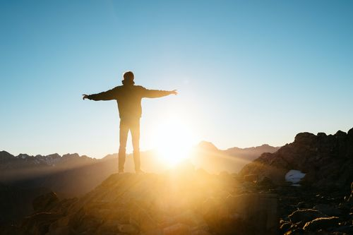 Man standing looking at sun on top of mountain in cold weather