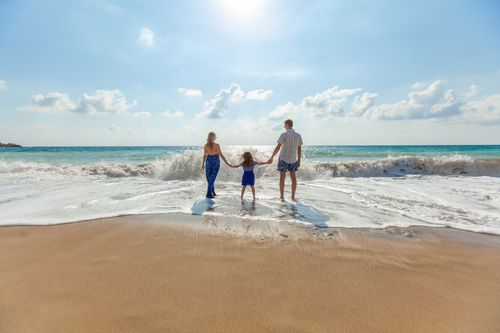 Family of three walking along sandy beach and ocean waves