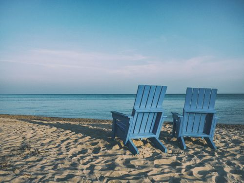 Two chairs on a clear sandy beach with blue ocean water view