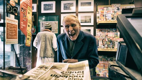 Laughing old man in shop looking at news papers and magazines