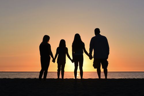 Family of four standing and holding hands on beach with sunset