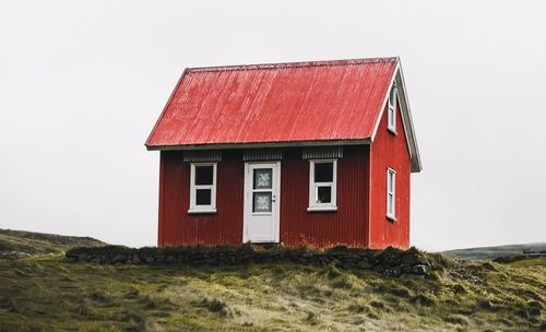 Red wooden house with white windows grey sky on grass