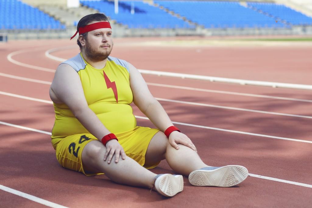 Ein fülliger Läufer in Supermankluft sitzt auf dem Tartanboden.