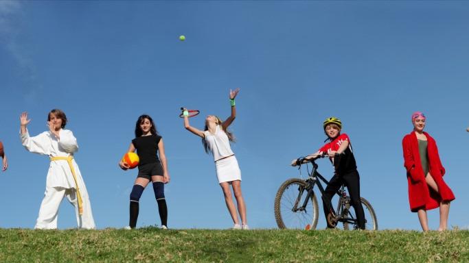 Sportliche Kinder stehen auf einem Hügel und wollen loslegen. Sie tragen Sportkleidung und Equipment, die sie für ihre Sportart brauchen.   Spiele.de